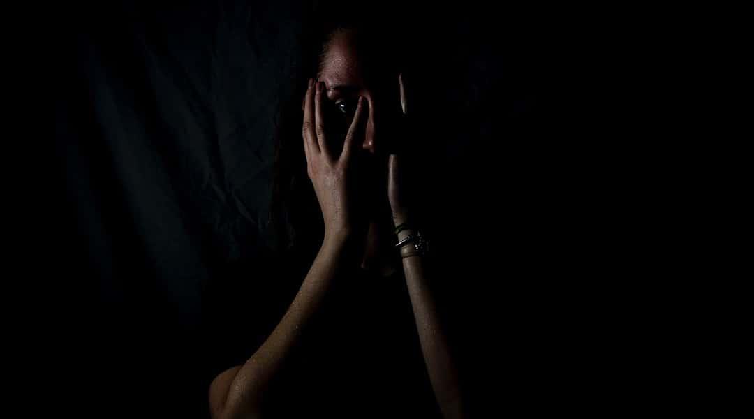 Femme apeurée se couvre le visage avec ses mains