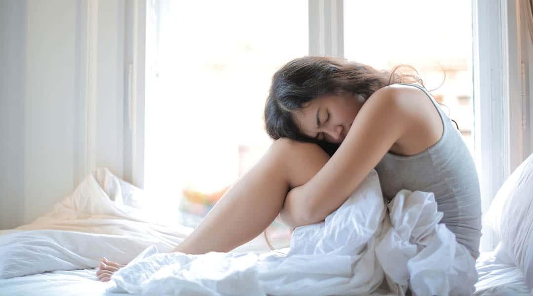 femme dans le lit souffre du ventre